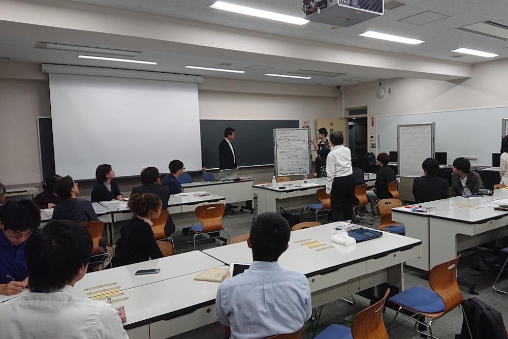 人々が教室に集い、話し合いをしている様子