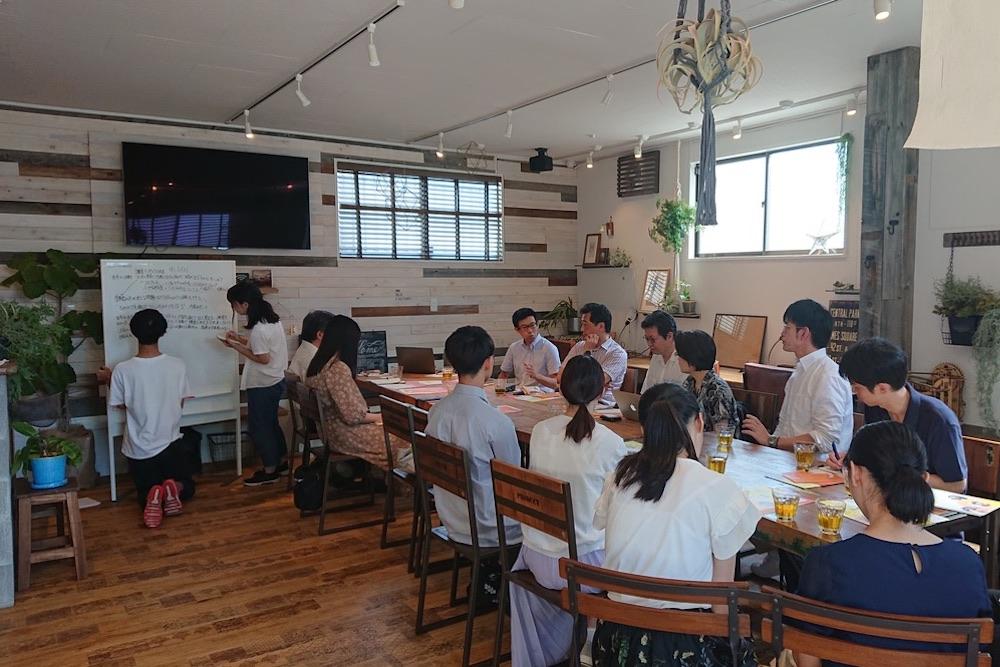 大きなテーブルを囲んで座るワークショップ参加者